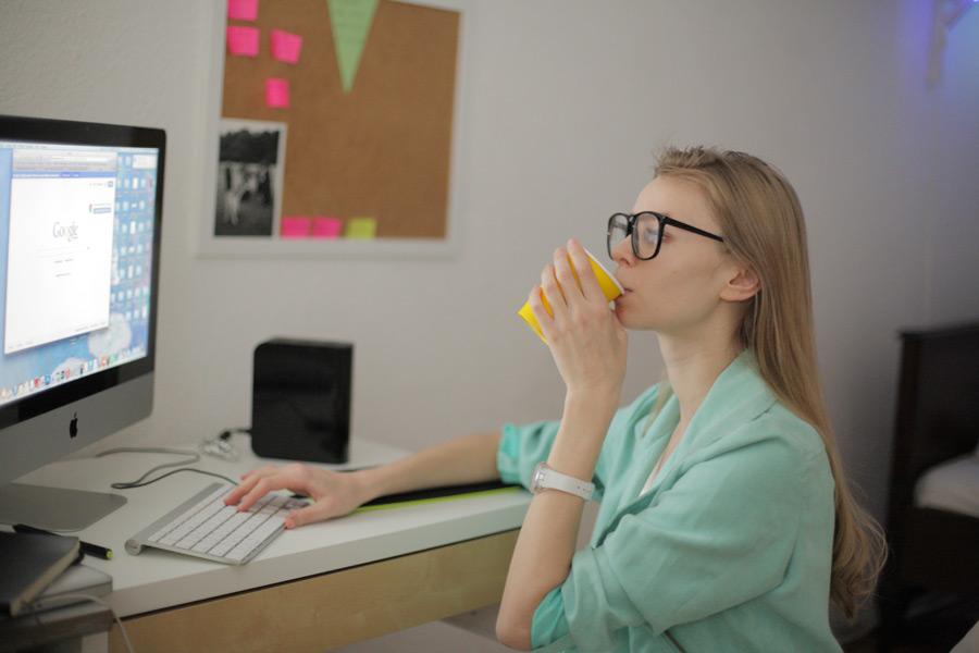フリー写真 パソコンの画面を見ながら飲む外国人女性