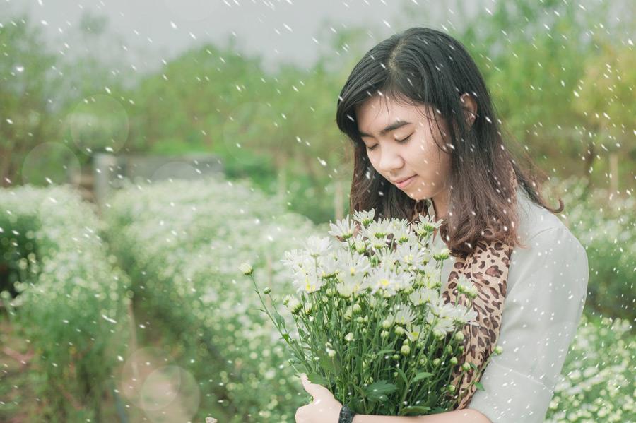 フリー写真 降りゆく雪と花を抱えるベトナム人女性