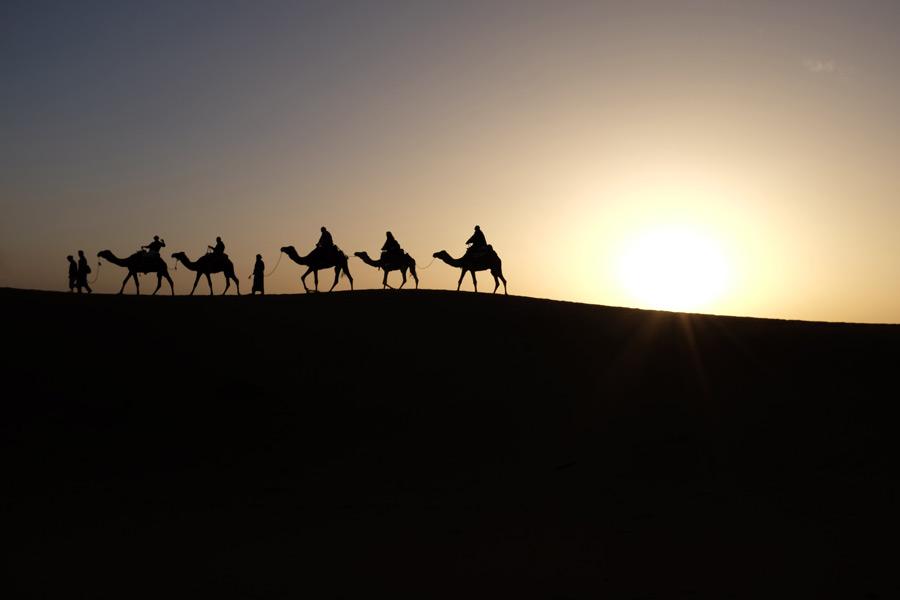 フリー写真 夕暮れのサハラ砂漠とラクダに乗る人々