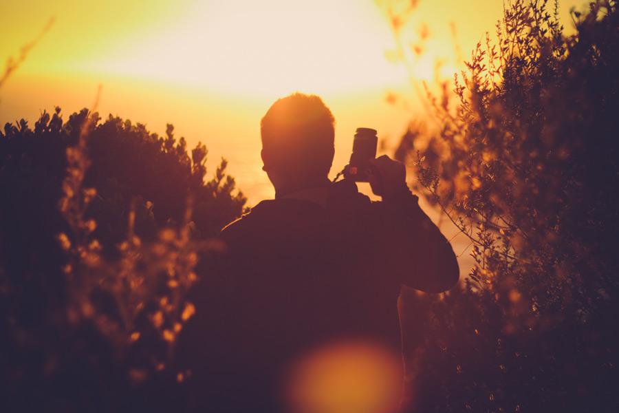 フリー写真 夕陽とカメラを持つ男性の後ろ姿