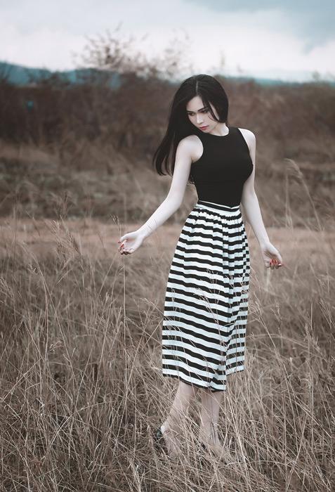 フリー写真 枯れた草むらに立つ女性