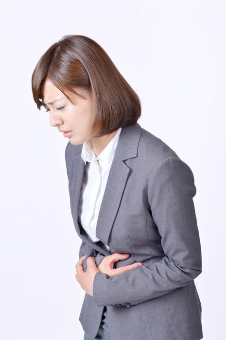 フリー写真 お腹が痛い日本の女性社員