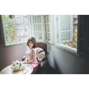 フリー写真, 人物, 女性, アジア人女性, 女性(00129), ベトナム人, アオザイ, 人と花, 花束, 白色の花, 窓辺, 座る(椅子), 俯く(下を向く)