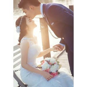 フリー写真, 人物, カップル, 花婿(新郎), 花嫁(新婦), ウェディングドレス, タキシード, キス(口づけ), 愛(ラブ), 結婚式(ブライダル), 人と花, ブーケ, 目を閉じる, 座る(椅子), 手を取る, 二人