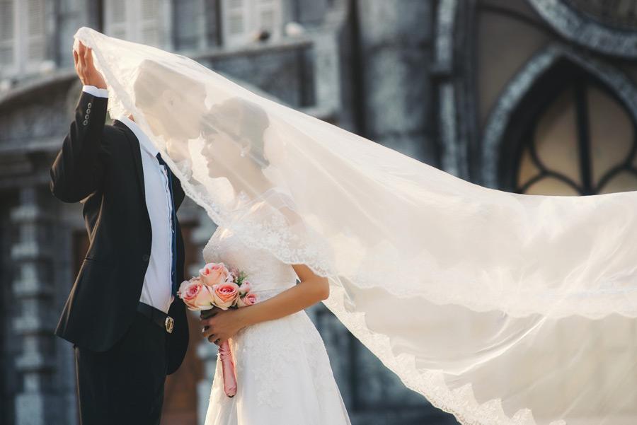 フリー写真 ベールの中で新婦の額にキスをする新郎