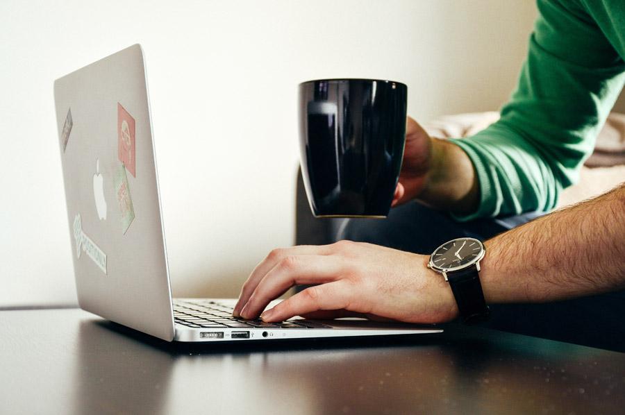 フリー写真 マグカップを持ちながらパソコンを操作する手