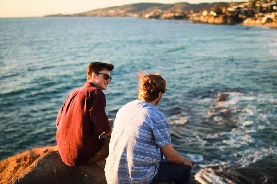 フリー写真 海岸の岩に座って語り合う二人のアメリカ人男性