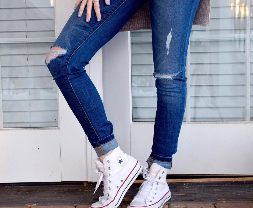 フリー写真 ダメージジーンズとスニーカーを履いた女性の脚