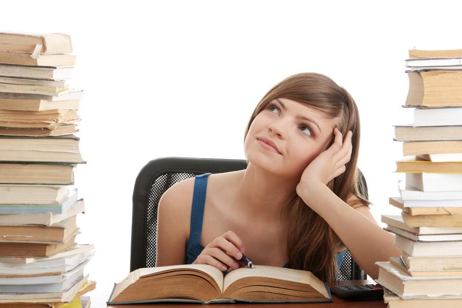 フリー写真 本に囲まれて夢想している女子大学生