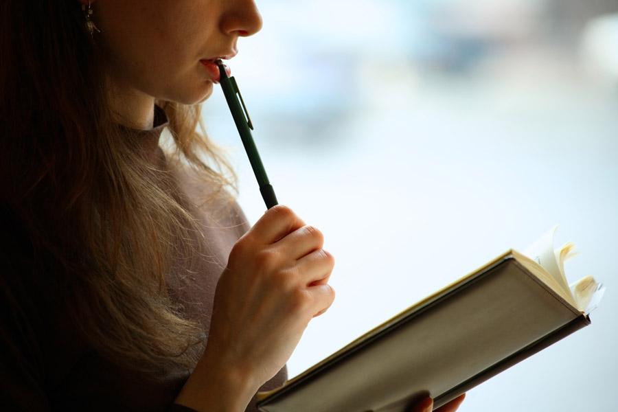 フリー写真 本を読みながら考え込む女子大学生