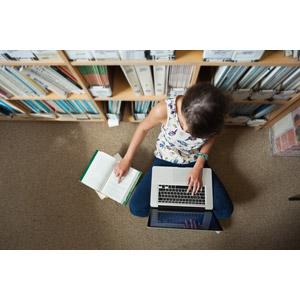 フリー写真, 人物, 少女, 外国の少女, 図書館, 勉強(学習), 本(書籍), パソコン(PC), ノートパソコン, 座る(床), あぐらをかく, 本棚