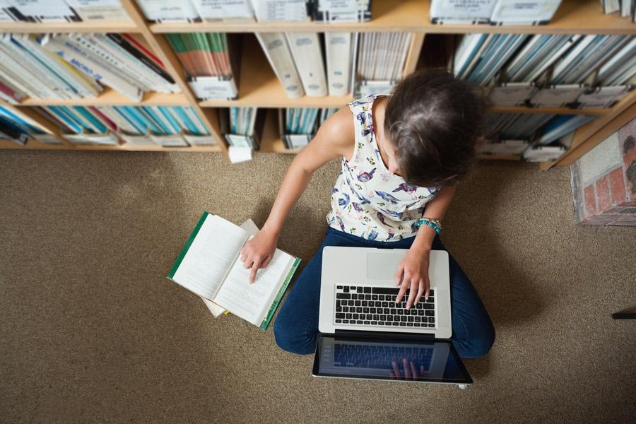 フリー写真 図書館でレポートを作成している少女