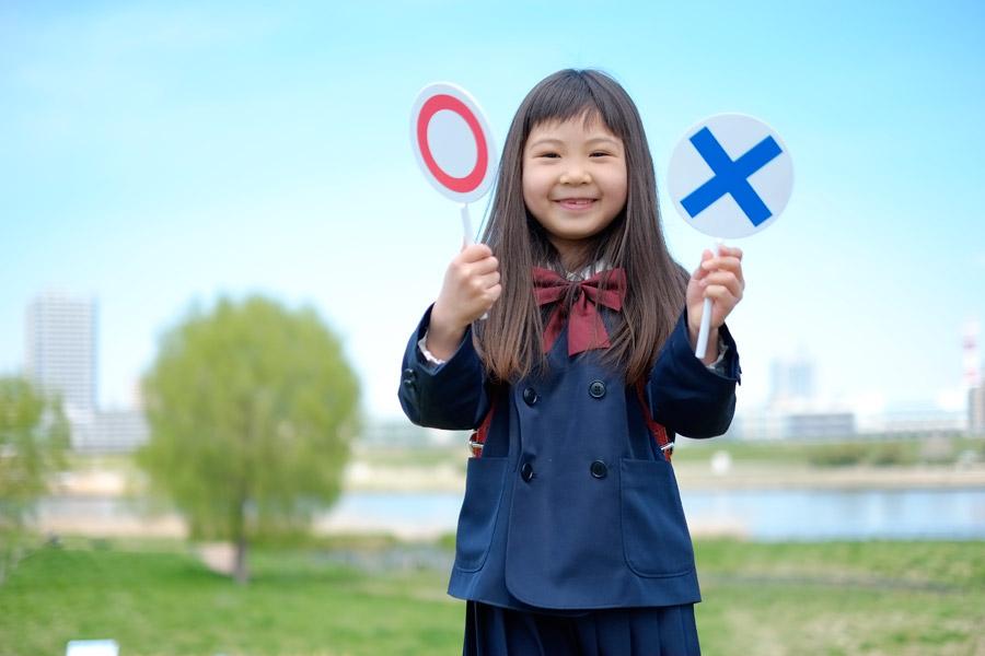 フリー写真 マルバツ札を持つ小学生の女の子