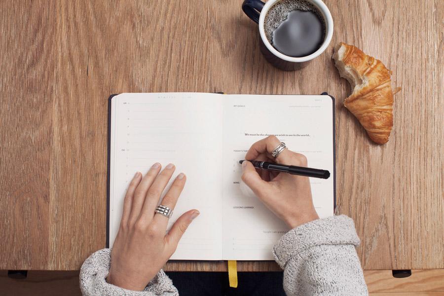 フリー写真 システム手帳に書き込む手とパンとコーヒー