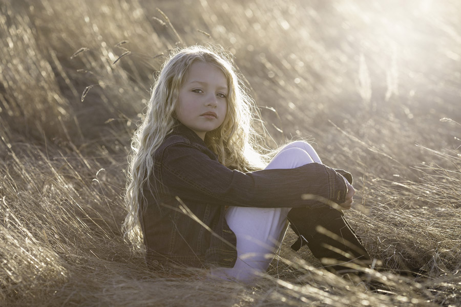 フリー写真 枯れ草の上に座る外国の女の子
