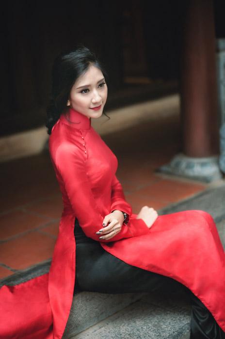 フリー写真 赤いアオザイ姿で階段に座るベトナム人女性