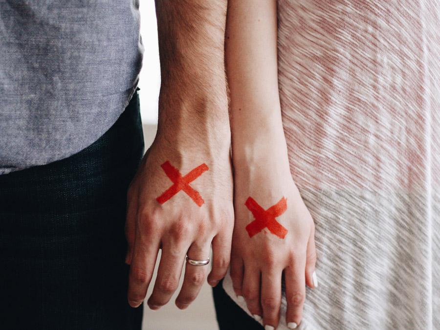フリー写真 バツ印の付いたカップルの手