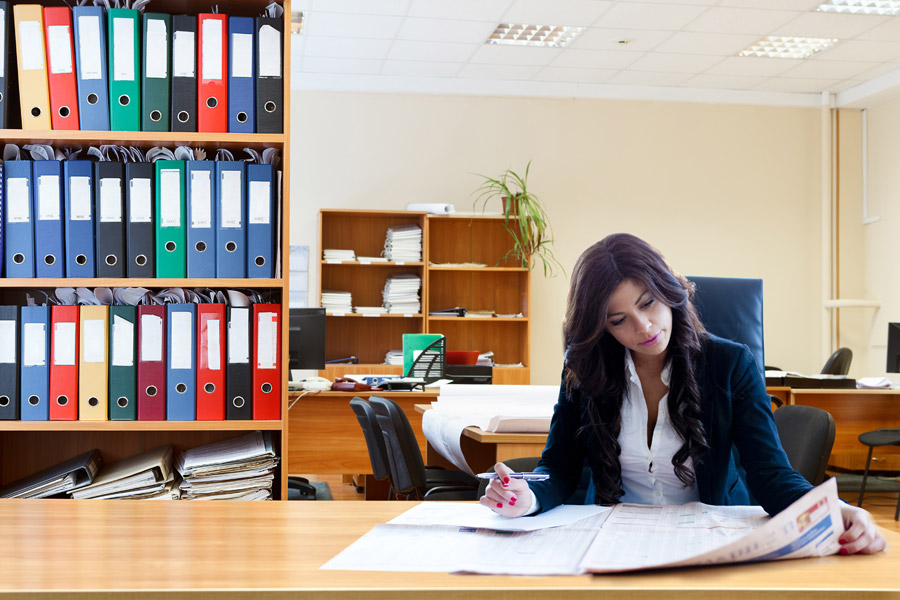 フリー写真 オフィスで新聞をチェック中のビジネスウーマン