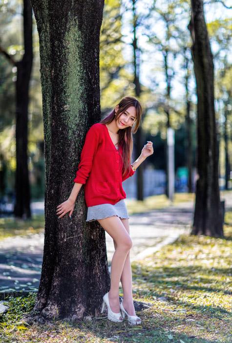 フリー写真 木にもたれかかる女性の全身ショット