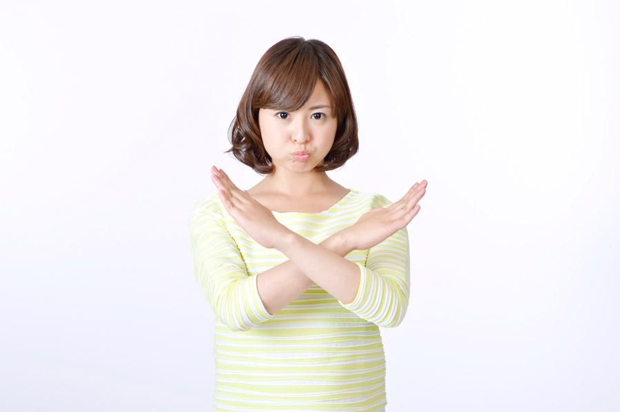 フリー写真 手をクロスさせてバツを作る日本人女性