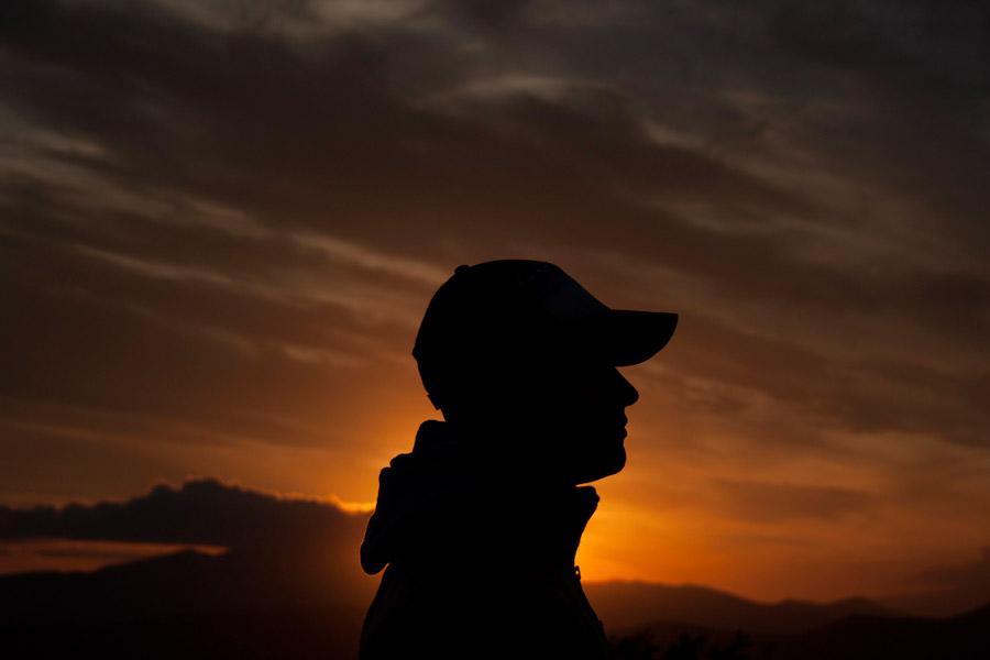 フリー写真 キャップを被る男性の横顔と夕陽