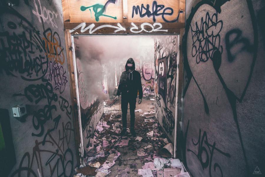 フリー写真 落書きされた廃墟の中で発煙筒を焚く人物
