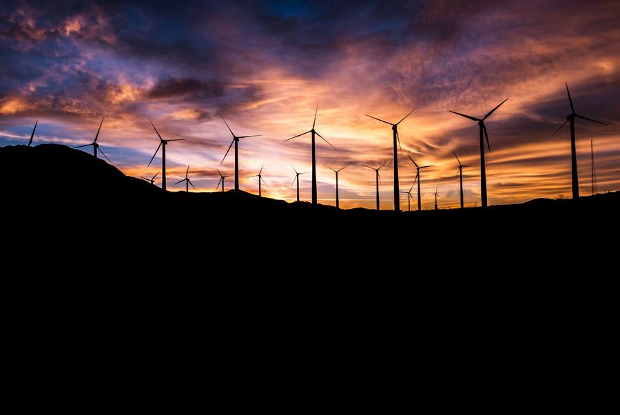フリー写真 夕陽と風力発電機群の風景