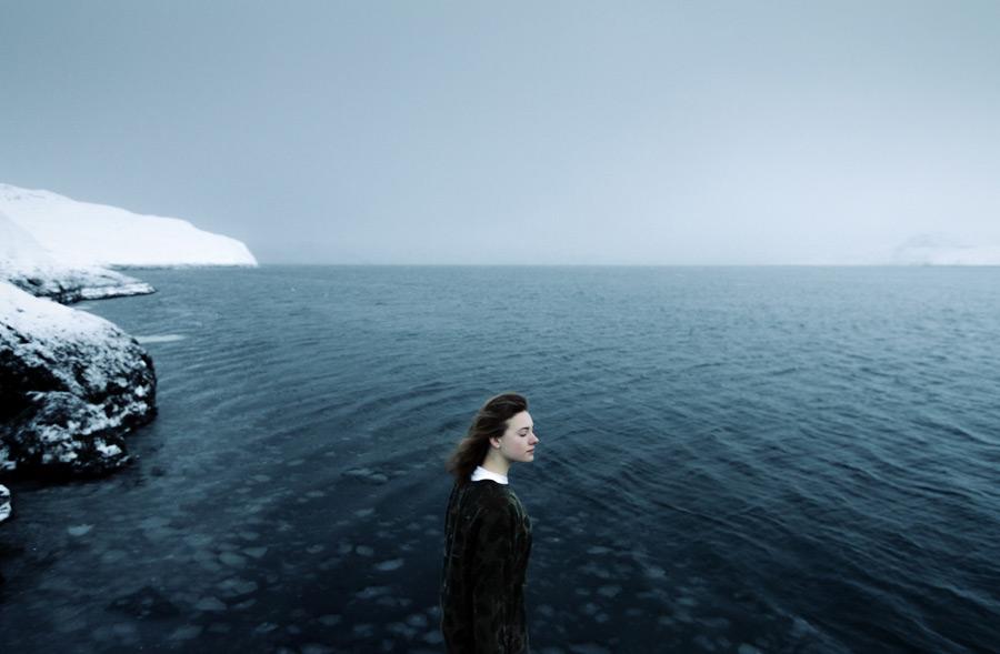 フリー写真 目を閉じるロシア人女性と海の風景