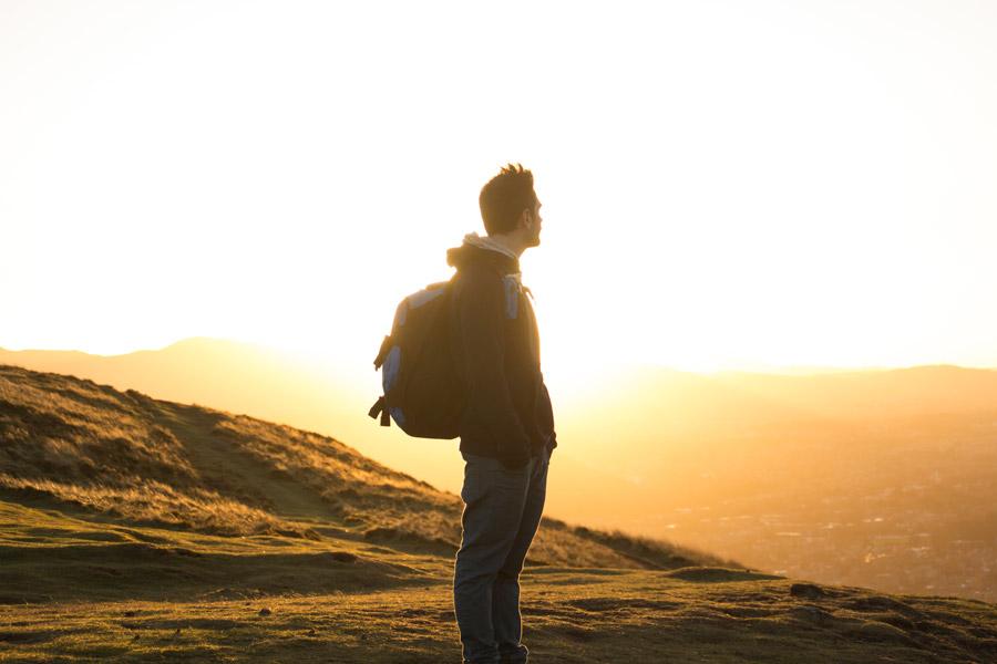 フリー写真 朝日と山の上から街を見下ろす登山者