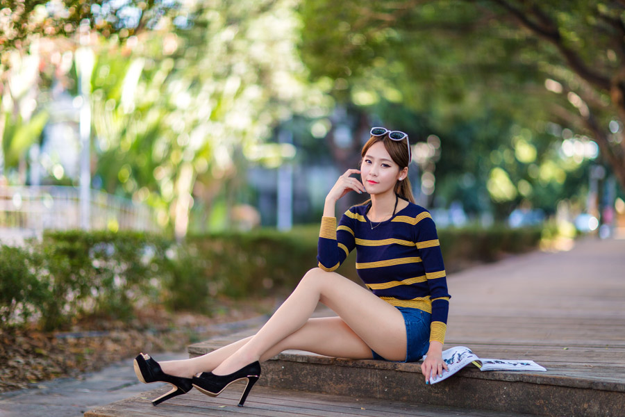 フリー写真 ショートパンツ姿でウッドデッキに座っている女性