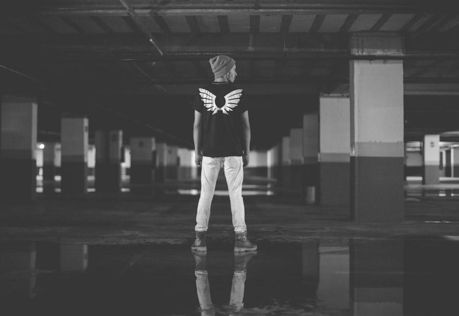 フリー写真 Tシャツに描かれた羽と駐車場に立つ男性