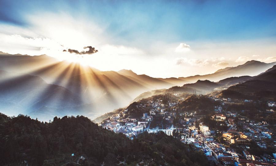 フリー写真 山の上から降り注ぐ朝日と街の風景