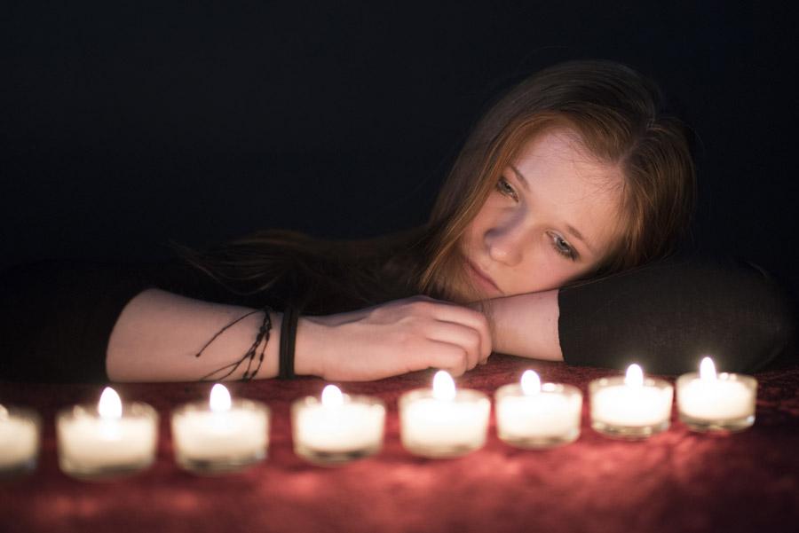 フリー写真 ろうそくの灯りと悲しげな表情の外国人女性