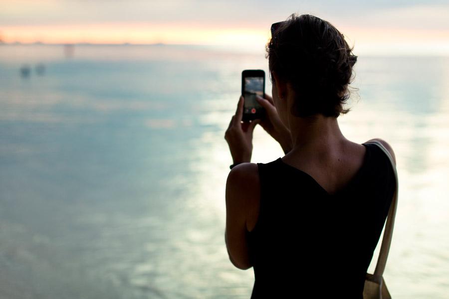 フリー写真 夕暮れの海とスマホで写真を撮る女性