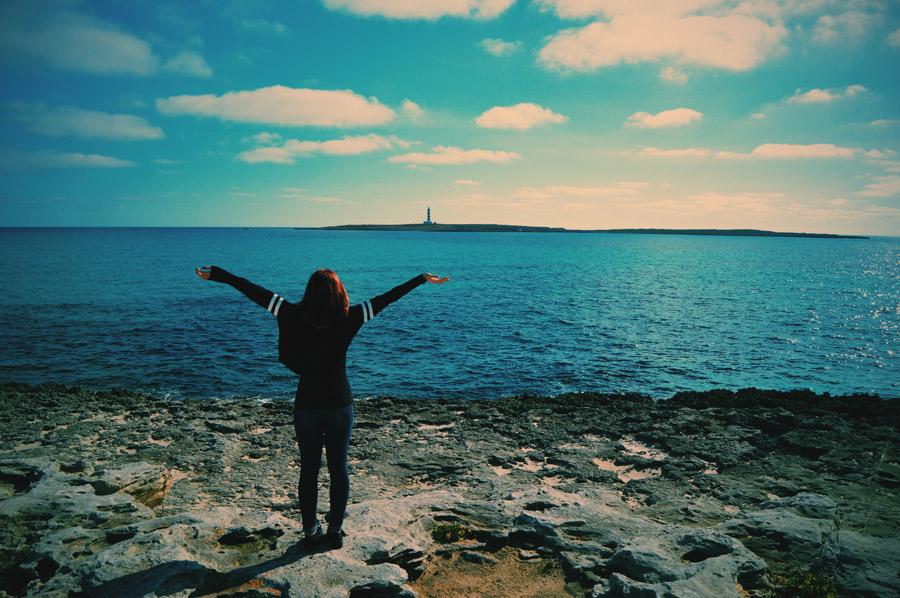 フリー写真 海岸で手を広げている女性の後ろ姿