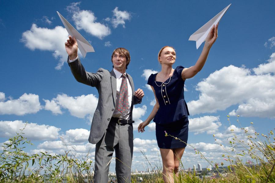 フリー写真 草むらで紙ひこうきを飛ばすカップル