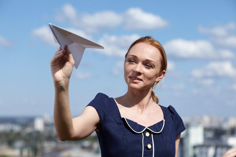 フリー写真 紙飛行機を手に持つ外国人女性