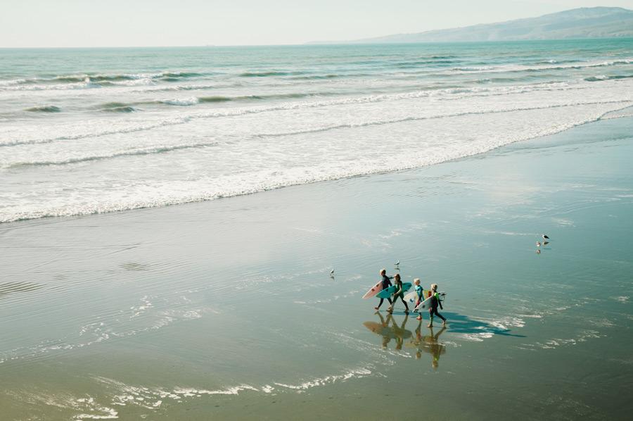 フリー写真 浜辺を歩く四人のサーファー