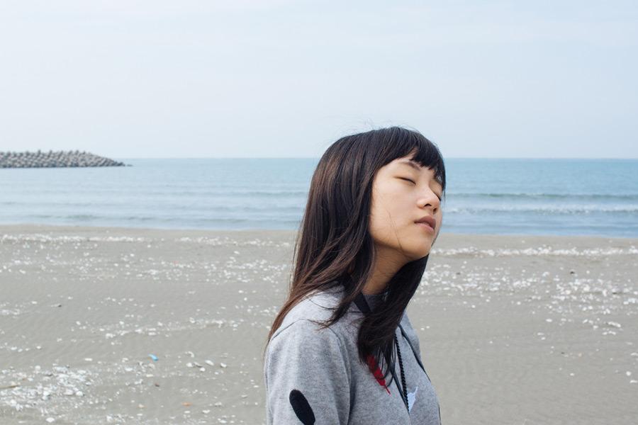 フリー写真 浜辺で目を閉じる少女
