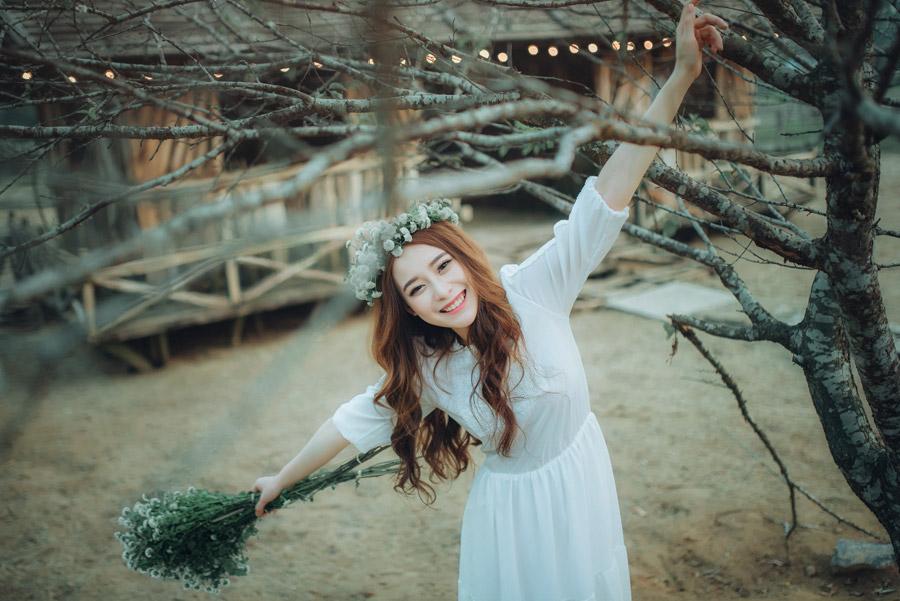 フリー写真 木の枝と手を広げる女性のポートレイト