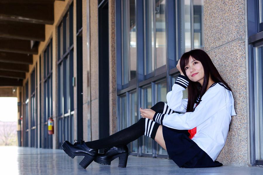 フリー写真 セーラー服姿で廊下に座る女子高生