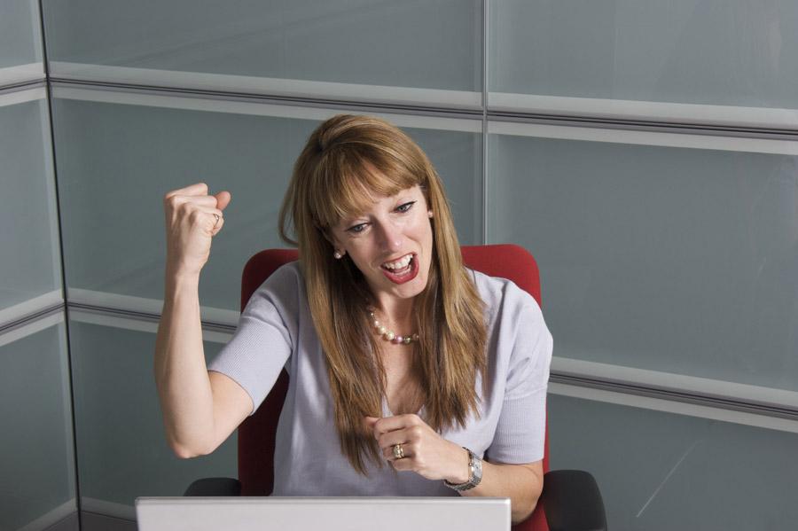 フリー写真 パソコンの画面を見ながらガッツポーズする女性社員