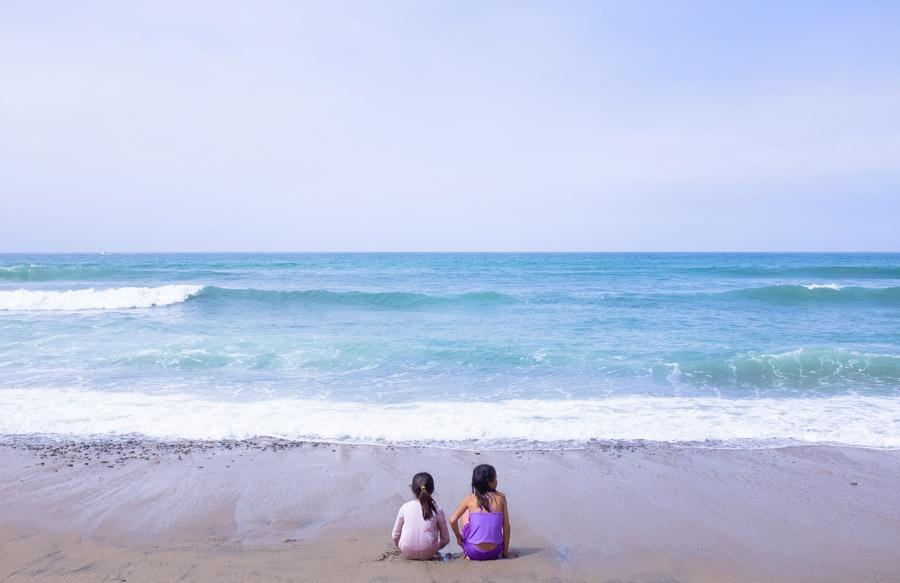 フリー写真 波打ち際に座る二人の姉妹