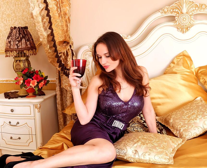 フリー写真 ベッドの上でワインを飲む女性