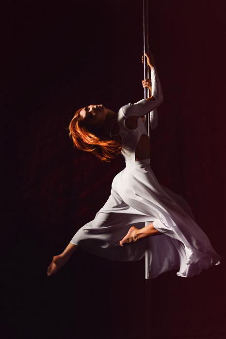 フリー写真 黒背景とポールダンスする女性