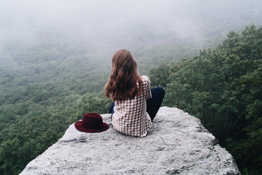 フリー写真 山頂の岩に座る女性の後ろ姿