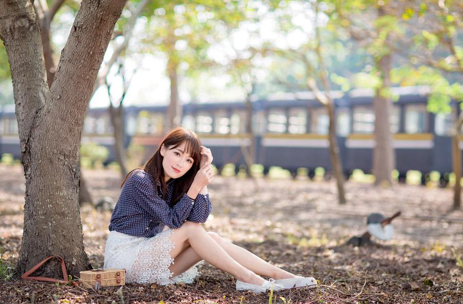 フリー写真 木の前に座っている女性のポートレイト