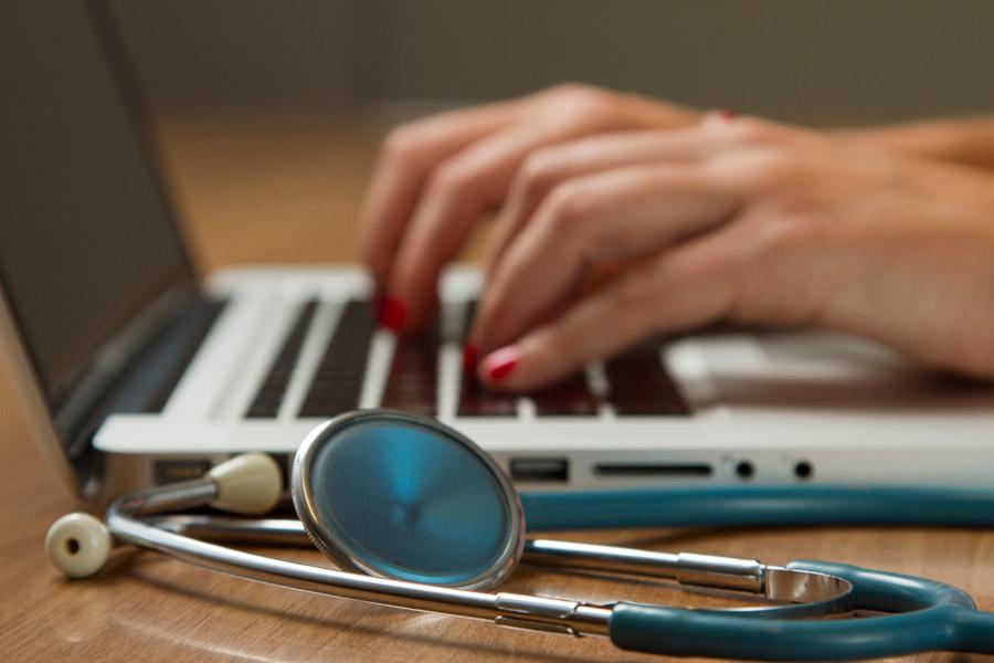 フリー写真 聴診器とノートパソコンと女性医師の手