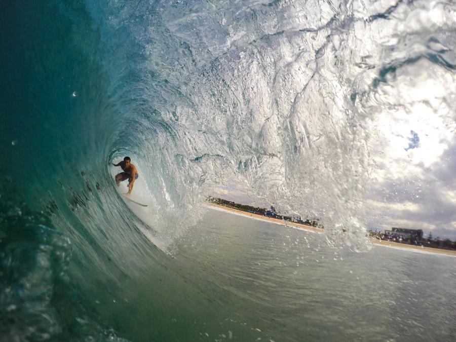 フリー写真 波のトンネルに挑むサーファー