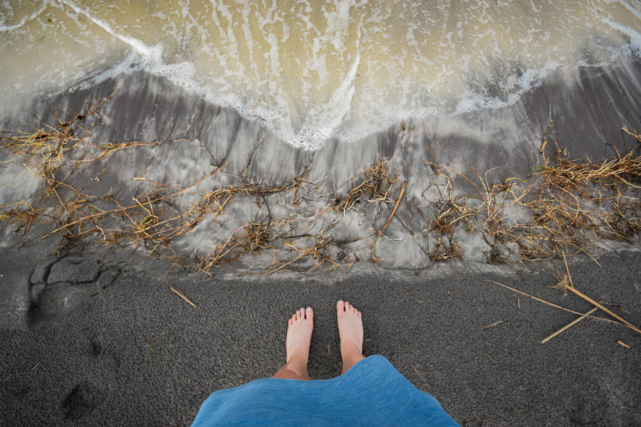 フリー写真 波打ち際に立つ女性の足